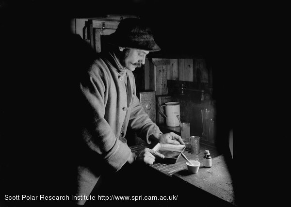 Herbert Ponting at work in the Darkroom at Winterquarters Hut. July 22nd 1911