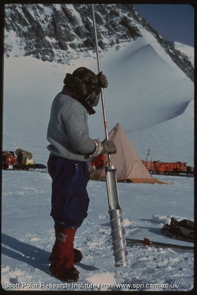 Oliver Shepard stands on snow holding ice core drill during the Transglobe Expedition 1979-82.